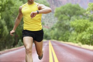Runner with heart rate monitor sports watch. Man running looking at his pulse outside in nature on road. Similar: